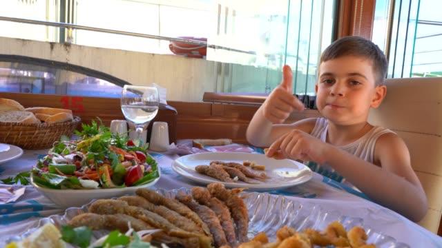 little boy eats fish in restaurant - fried stock videos & royalty-free footage