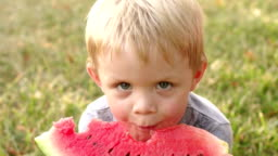 A little boy eats watermelon in the Park in summer