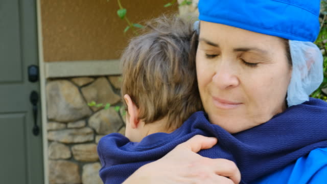 little boy embracing his mother who is a healthcare worker and he did not see for weeks because she was busy curing people because covid-19 - heroes stock videos & royalty-free footage