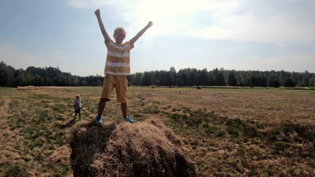 little boy enjoying climbing straw bale - bale stock videos & royalty-free footage