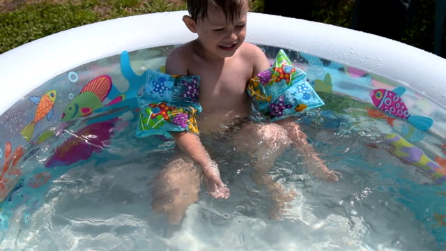 Little boy enjoying summer day bathing in his own pool