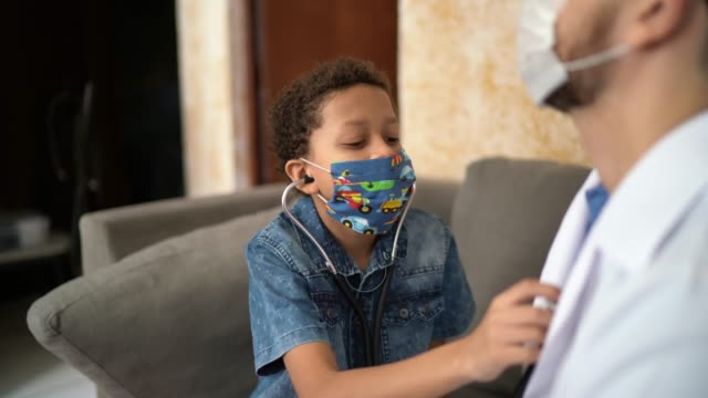 little boy examining and embracing doctor while listening to heartbeat - stethoscope stock videos & royalty-free footage