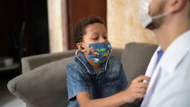 vídeos de stock e filmes b-roll de little boy examining and embracing doctor while listening to heartbeat - estetoscópio