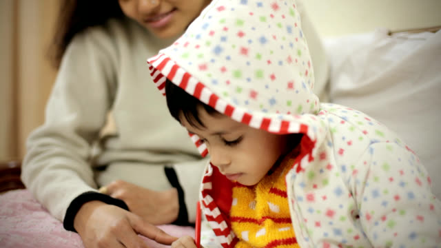 Little boy filling color in coloring book with his mother