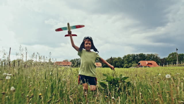 vídeos de stock e filmes b-roll de slo mo little boy flying airplane across the grass - corredor objeto manufaturado