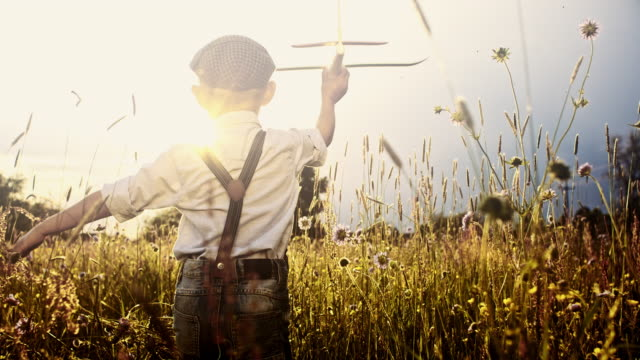slo mo little boy flying airplane while running through meadow - daydreaming stock videos & royalty-free footage
