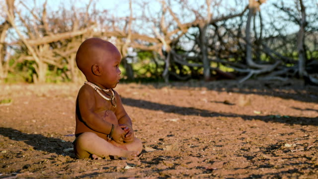 little boy from the Himba tribe crawling on the ground in nomadic village