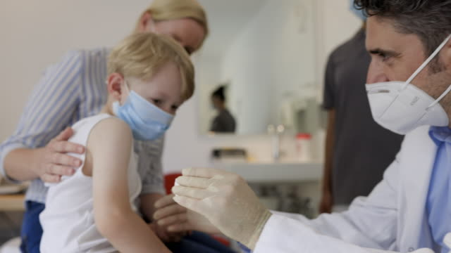 little boy getting a flu injection from pediatrician - kids stock videos & royalty-free footage