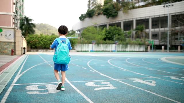 vídeos y material grabado en eventos de stock de little boy que van a la escuela - patio