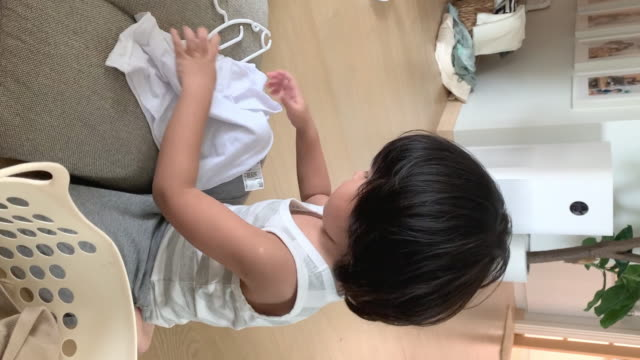 little boy hanging wet baby clothes on hanger at home. - baby boys stock videos & royalty-free footage