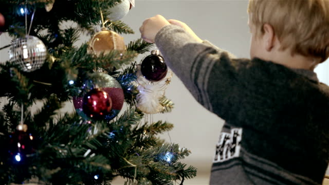little boy hangs bauble on christmas tree - hanging stock videos & royalty-free footage