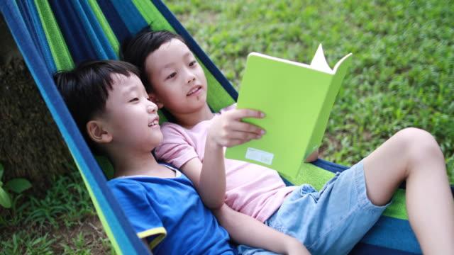 小さな男の子はハンモックで休む - ハンモック点の映像素材/bロール