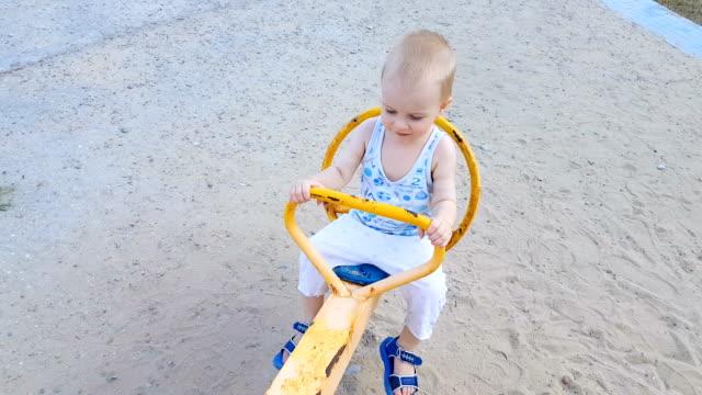 vídeos y material grabado en eventos de stock de niño divertirse en un subibaja - balancín