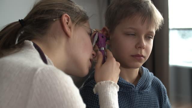 vidéos et rushes de petit garçon ayant un examen d'oreille - examen