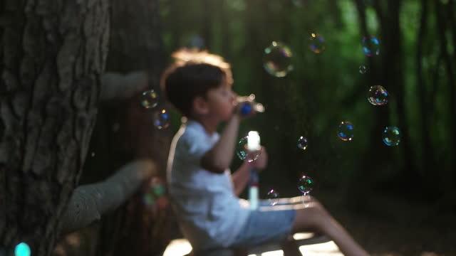 liten pojke som har kul blåser bubblor - bubbla bildbanksvideor och videomaterial från bakom kulisserna
