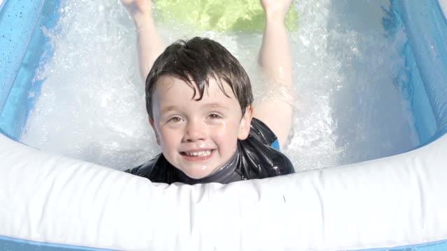 vidéos et rushes de petit garçon s'amusant dans une pataugeoire au ralenti - pataugeoire