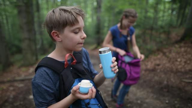 little boy hiker drinking from reusable water bottle. - bottle stock videos & royalty-free footage