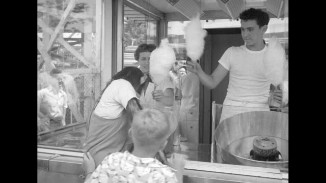 little boy hoists albert, a chimp wearing human clothing, to the counter of a cotton candy booth, and they enjoy the sugary confection - palisades park stock videos & royalty-free footage