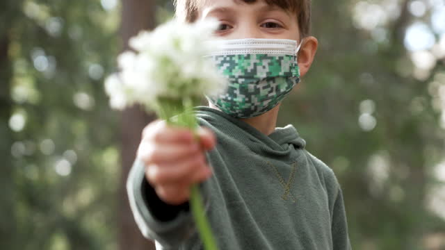 little boy holding a bouquet of flowers and wearing protective face mask - flower stock videos & royalty-free footage