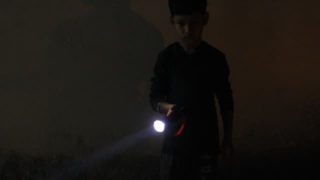 little boy holding a pocket torch light and searching in the darkness.