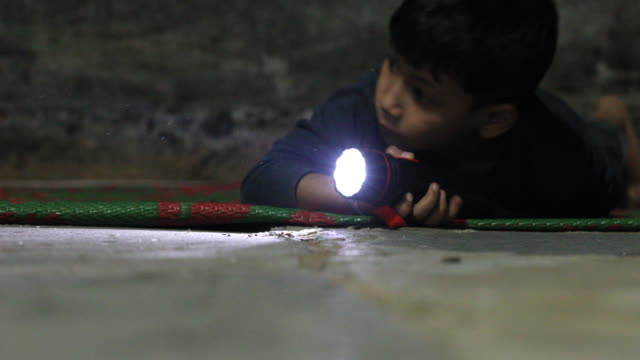 vídeos de stock e filmes b-roll de little boy holding a pocket torch light and searching in the darkness. - searching