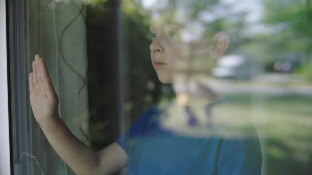 vidéos et rushes de slo mo. little boy holds his hand aganist glass window. - être seul