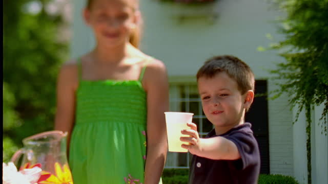 A little boy holds out a cup of lemonade after getting the drink from his sister.