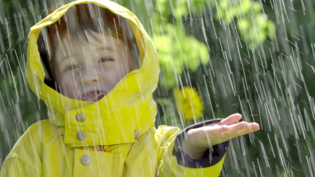 A little boy holds out his hand and sticks out his  tongue as he stands in the rain.