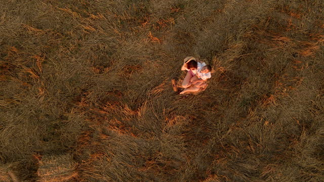 little boy hugging his mother sitting on a hay. aerial view - two generation family stock videos & royalty-free footage