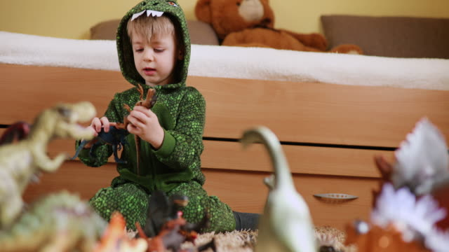 kleiner junge in einem dinosaurier-kostüm spielen mit seinen dinosauriern - baby boys stock-videos und b-roll-filmmaterial