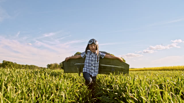 slo mo little boy in a jet pack costume running in a wheat field - ideas stock videos & royalty-free footage