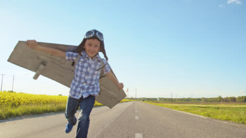 slo mo little boy in a jet pack costume running toward camera - mid air stock videos & royalty-free footage