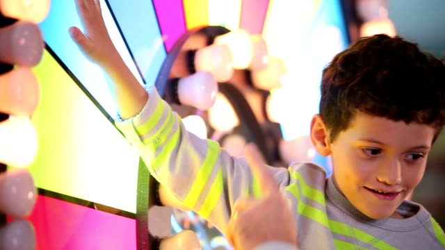little boy in arcade playing with wheel - school fete stock videos and b-roll footage