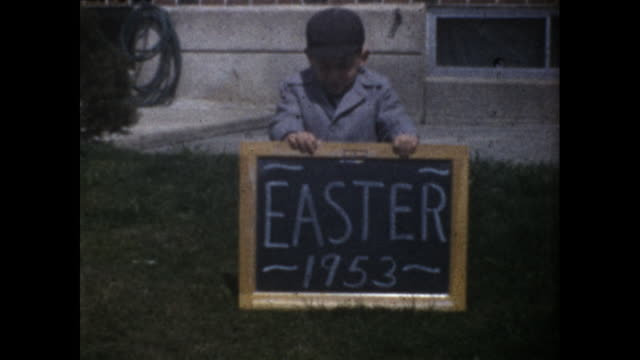 """little boy in black cap holding a small blackboard with the words """"easter 1953"""" on lawn - one boy only stock videos & royalty-free footage"""