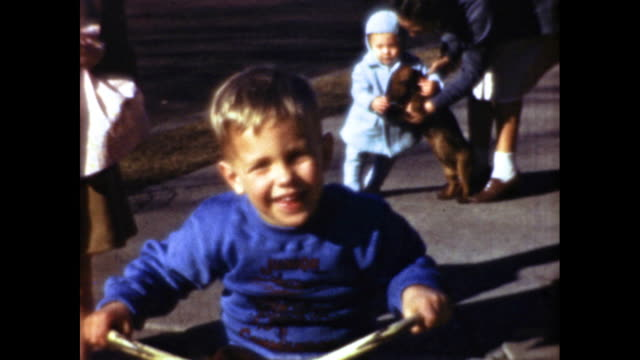 little boy in blue sweatshirt smiling and riding a bicycle toward camera on the sidewalk man talking to toddler and dog in the background - sweatshirt stock videos & royalty-free footage