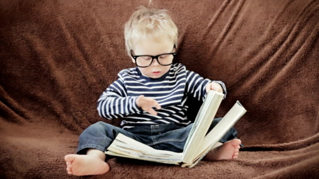 little boy in glasses reading book - reading glasses stock videos & royalty-free footage