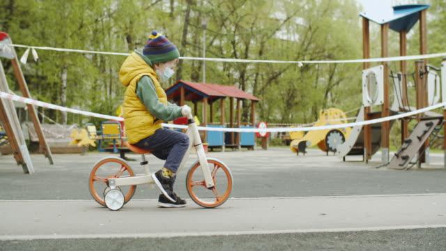 居心地の良い-19の流行のために閉鎖された遊び場の近くのランバイクの保護マスクを着た小さな男の子 - 禁止点の映像素材/bロール