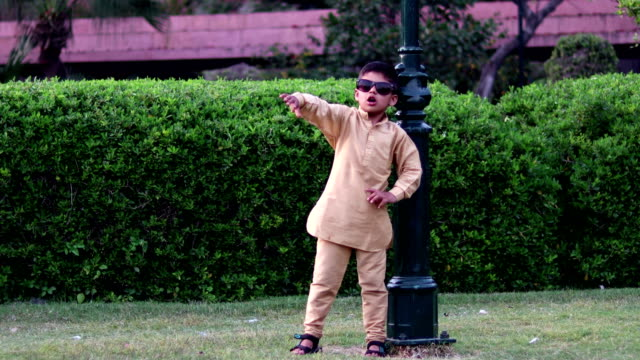 little boy in sunglasses and having fun dancing in summer park - pyjamas stock videos & royalty-free footage