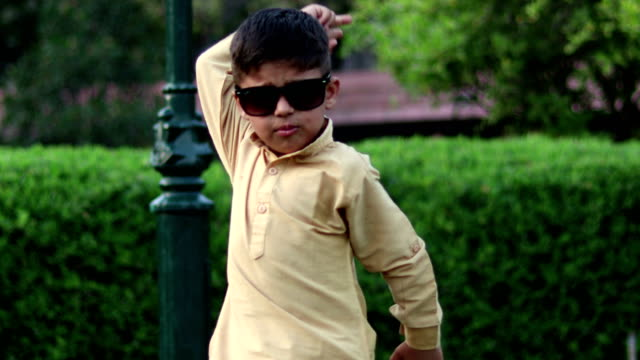 little boy in sunglasses and having fun dancing in summer park - indian subcontinent ethnicity stock videos & royalty-free footage