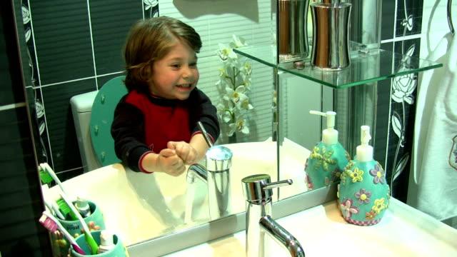 vídeos de stock, filmes e b-roll de menino no banheiro - pia instalação doméstica