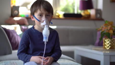vidéos et rushes de petit garçon dans le masque d'inhalation avec des soucis de respiration - 4 5 ans
