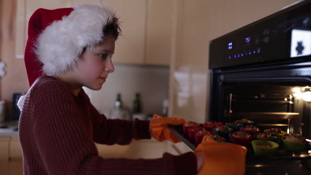 little boy inserting baking sheet full of cookies to the oven. - baking tray stock videos & royalty-free footage