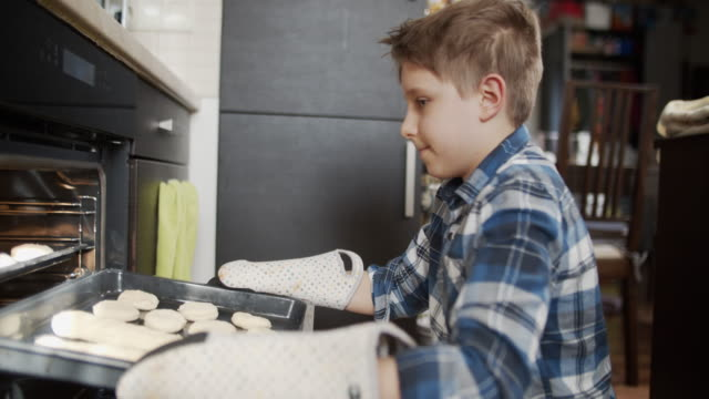 little boy inserting cooking tray with buns and baguettes to the oven - inserting stock videos & royalty-free footage