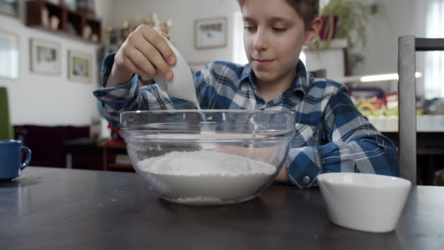 little boy is adding sugar to the bowl with flour - french food stock videos & royalty-free footage