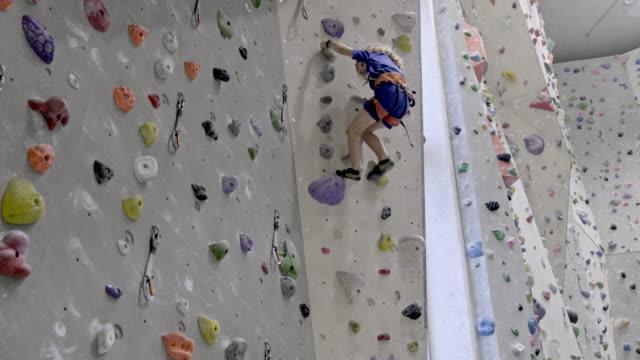 little boy is climbing an indoor climbing wall - climbing equipment stock videos & royalty-free footage