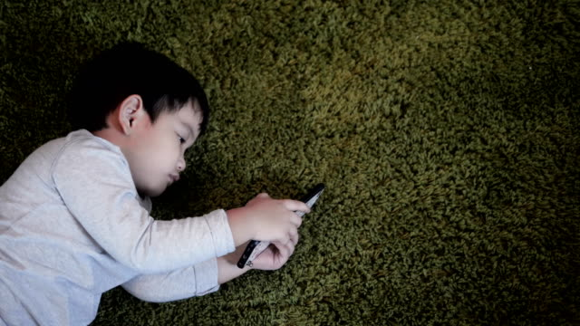 stockvideo's en b-roll-footage met kleine jongen is liggend op de vloer in huis en spelen met mobiele - videoportret