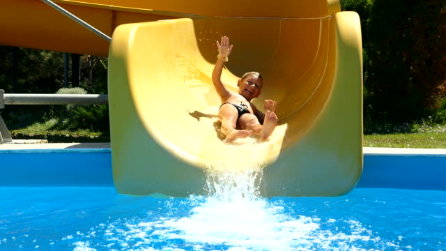little boy is riding a water slide in an aquapark - water slide stock videos & royalty-free footage