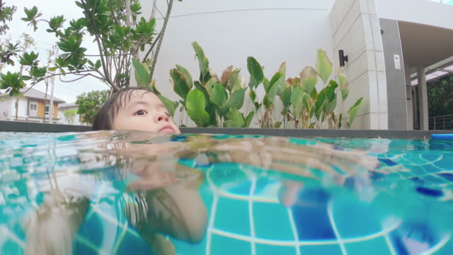 little boy is swimming and playing in the pool - inflatable stock videos & royalty-free footage