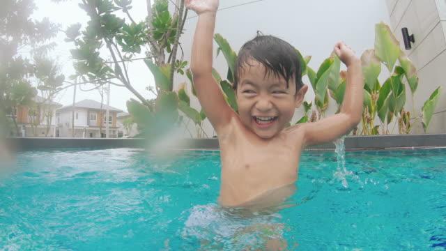 kleiner junge schwimmt und spielt im pool - schwimmflügel stock-videos und b-roll-filmmaterial