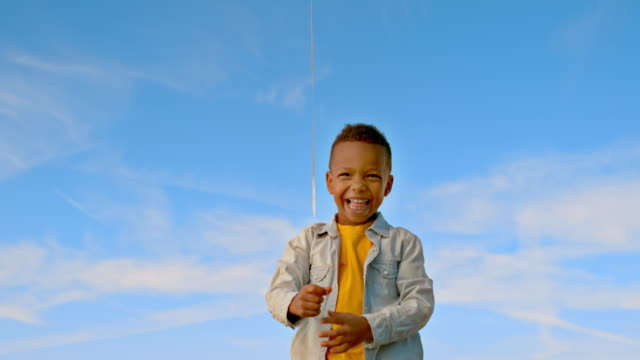 slo mo little boy jumping and smiling after letting his balloon float up into the sky - solo un bambino maschio video stock e b–roll